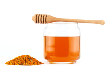 Honey in jar with dipper and pollen on isolated background