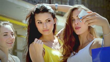 Three pretty girls-shopaholic make selfie after shopping