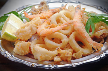 Fried calamari and shrimps on wooden table