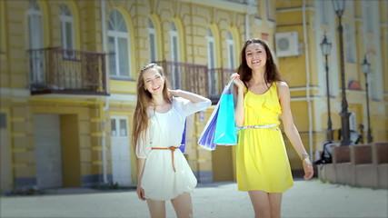 Two girls shopaholic with beautiful slim legs walking to the sho