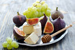 canvas print picture - Delicious snack cheese, figs and grapes. Wooden background