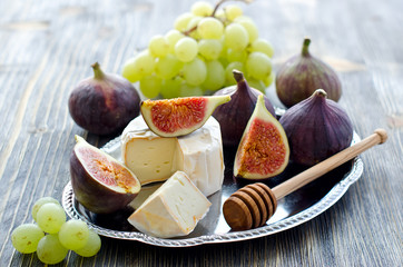 Delicious snack cheese, figs and grapes. Wooden background