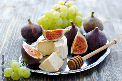 canvas print picture Delicious snack cheese, figs and grapes. Wooden background