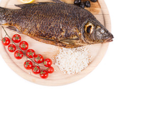 Grilled carp on platter with rice and tomatoes.