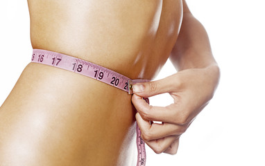 Woman measuring waist line with tape measure