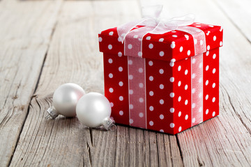 red Christmas gift box, polka dots, on wood background.