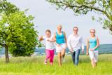 Familie rennt über Feld oder Wiese im Sommer