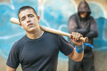 Aggressive teenager with a baseball bat on building background
