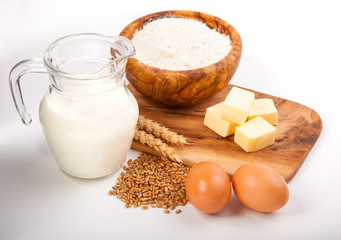 Glass jug with milk, wheat seeds, flour and two eggs on white ba