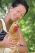 Frau hält lächelnd eine Henne fest