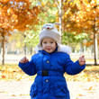 Portrait of child has fun outdoor. Little girl playing in autumn