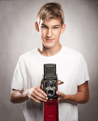 young man holding  a vintage camera on a gray background