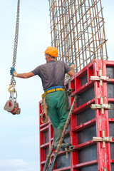 Construction worker mounting concrete formwork with tower crane