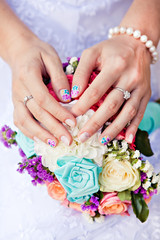 Colored manicure on a colored bouquet of flowers