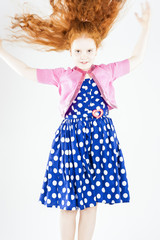 Happy Jumping Red-haired Caucasian Girl In Polka-Dotted Dress Pl