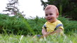 Cute baby boy having fun with soap bubbles on grass