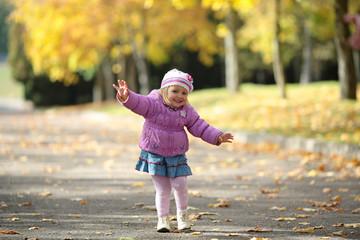 Happy child runs across the road in autumn park