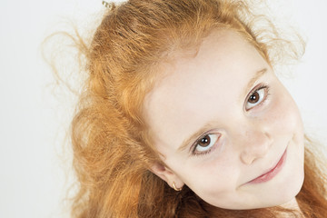 Closeup Natural Portrait of Little Red-haired Girl Looking Strai