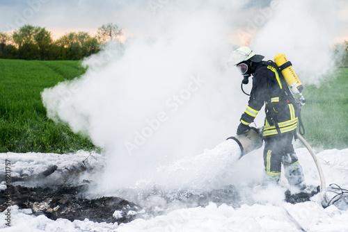 Leinwanddruck Bild Feuerwehrmann bei Löscharbeiten mit Schaummittel