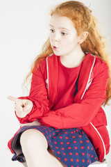 Pointing Little Red-haired Caucasain Girl with Surprised Express