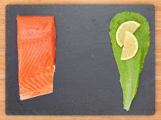 Fresh salmon fish with salad leaf and lemon