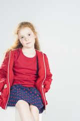 Fashionable Little Red-Haired Caucasian Girl In Studio. Against