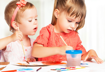 happy little girl in kindergarten draw paints