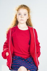 Portrait of Surprised Redhaired Caucasian Little Girl In Red Jac