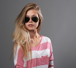 girl in sunglasses on gray background