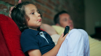 Father and son watching together television and talking