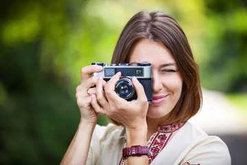 Young woman taking picture with retro camera outdoors
