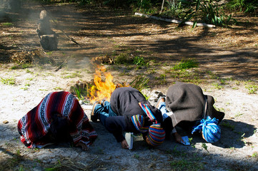 three mayan priests kissing ground