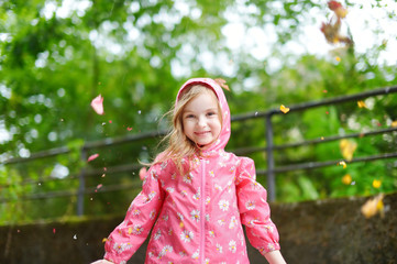 Adorable girl happily standing under the rain