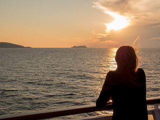 Girl looks at the sunset on the sea from the deck of a cruise bo