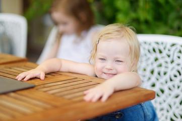Adorable toddler girl in an outdoor restaurant