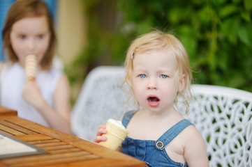 Two little sisters eating ice cream outdoors