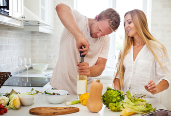 Young couple starting to drink a white wine at home