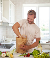 Man holding paper bag full of groceries on the kitchen