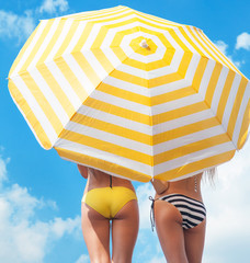 Women wearing bikini under a beach umbrella
