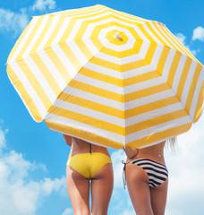 Women wearing bikini under a beach umbrella
