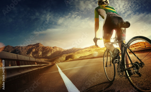 canvas print picture Cyclist riding a bike on an open road to the sunset