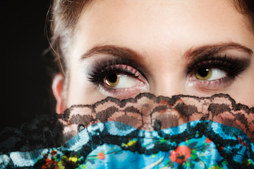 Face of girl flamenco dancer hidden behind fan