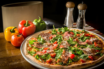 Pizza with rucola and Black Forest ham wooden table vegetables
