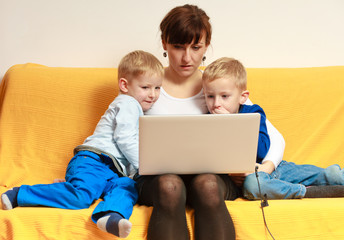 Happy family. Mother and sons using laptop