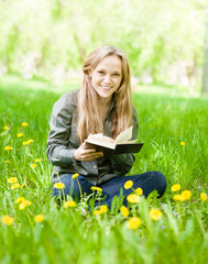 laughing girl sitting on grass with dandelions reading a book an