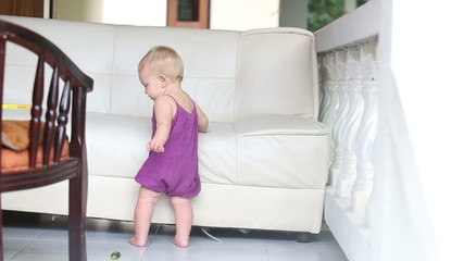child eating cucumber standing leaning on the sofa