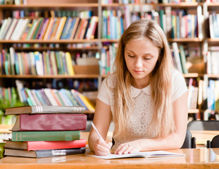 pretty female student with books working in a high school librar