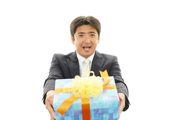 プレゼントを持つ笑顔のビジネスマン