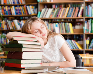 the tired student sleeps in library on pile books