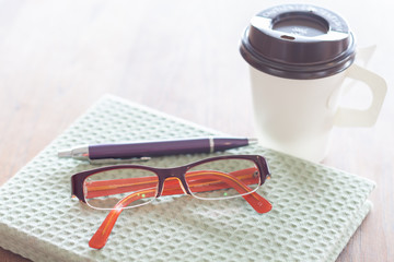 Notebook, pen eyeglasses and coffee cup on wooden table
